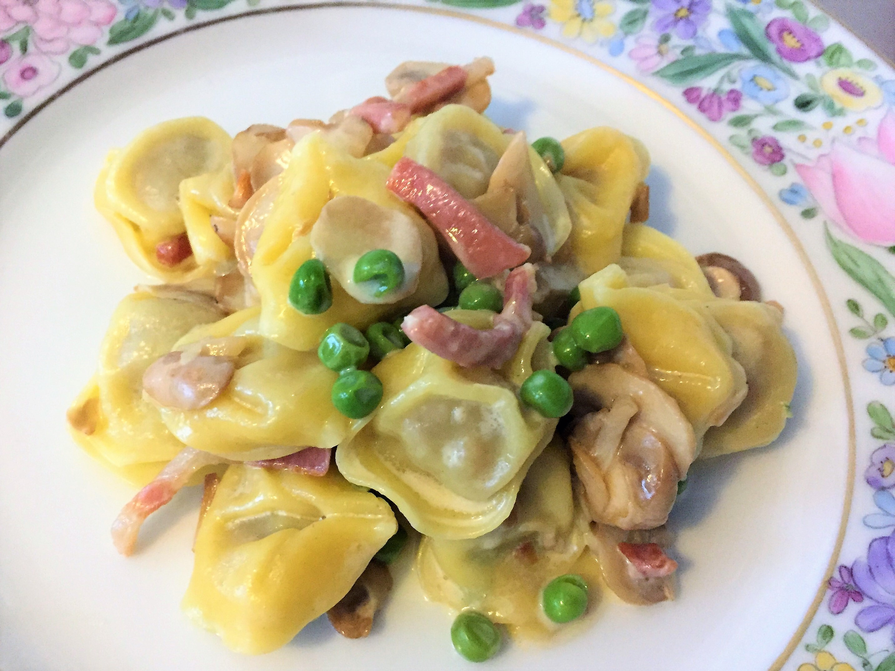 Tortelloni con champignon, piselli e pancetta affumicata