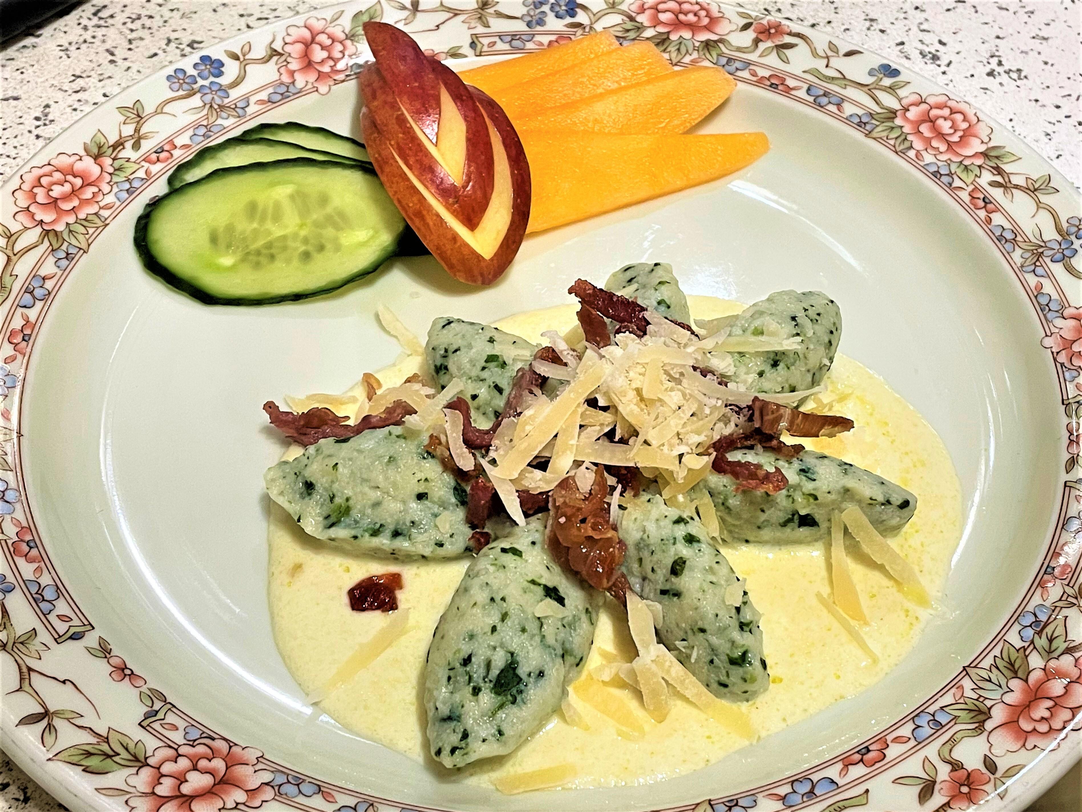Chenelle di ricotta e spinaci con crema di parmigiano e speck croccante